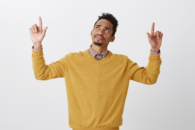 2階で何かを認識するのに苦労して混乱している男。アフロの髪型、手を挙げて、疑念と疑念を持って指差して見上げる美しい黒肌の男性モデルに質問