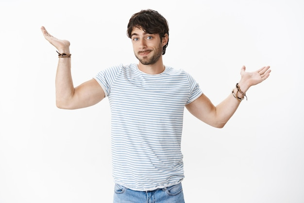 Confused guy not knowing answer, being clueless raising hands sideways with shoulder shrug and apology smirk standing unaware, being questioned and uncertain over gray wall