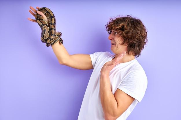 혼란 스 러 워 남자 손에 뱀을보고 보라색 배경 위에 절연 손실에 서