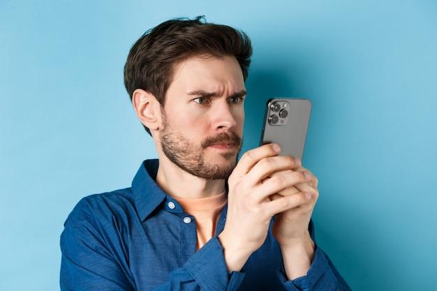 혼란 스 러 워 남자 휴대 전화 화면에서 가까이 응시 하 고 찡그림, 파란색 배경에 서.