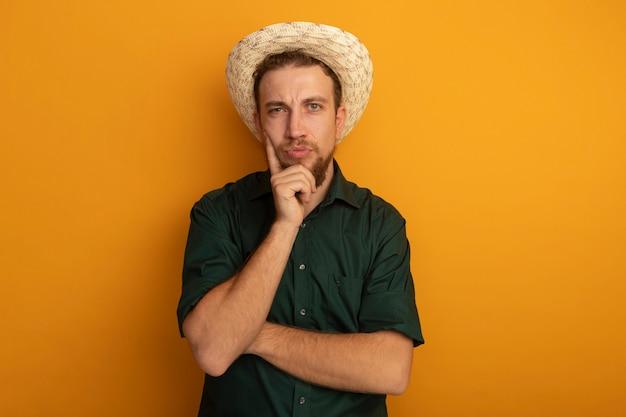 Uomo biondo bello confuso con cappello da spiaggia mette la mano sul mento isolato sulla parete arancione
