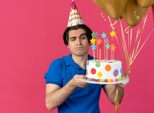 Confused handsome caucasian man wearing birthday cap holds helium balloons and birthday cake