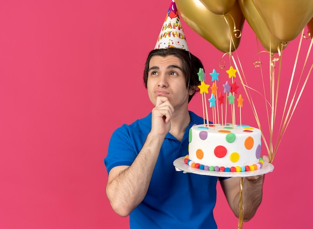Confused handsome caucasian man wearing birthday cap puts hand on chin holds helium balloons and birthday cake