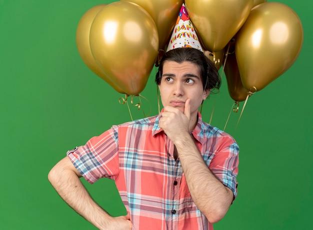 Un bell'uomo caucasico confuso che indossa un berretto da compleanno si trova di fronte a palloncini di elio che tengono il mento guardando di lato
