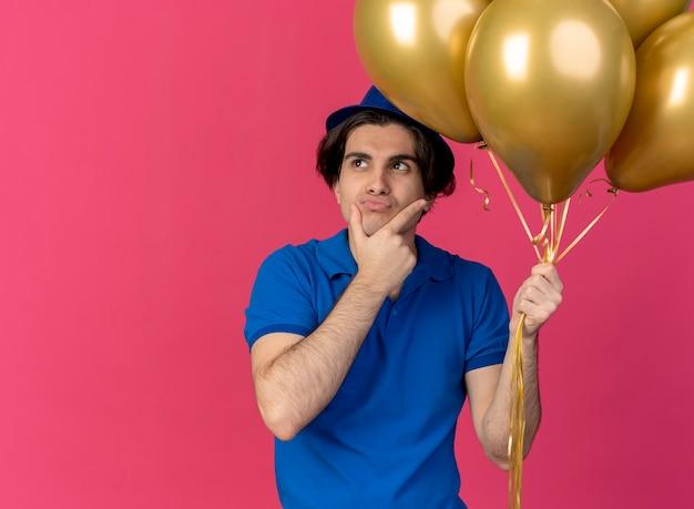 Un bell'uomo caucasico confuso che indossa un cappello da festa blu tiene palloncini di elio e mette la mano sul mento
