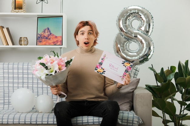 Confused handsome guy on happy women day holding bouquet with greeting card sitting on sofa in living room