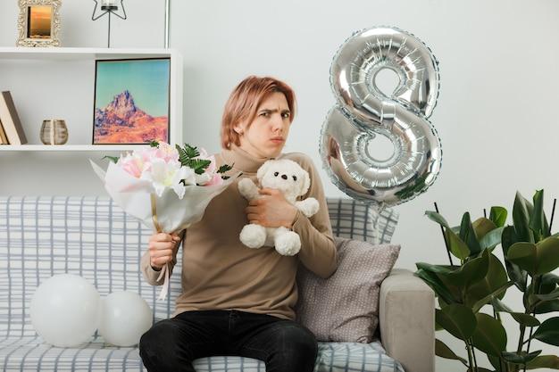 リビングルームのソファに座っているテディベアと花束を保持している幸せな女性の日に混乱したハンサムな男