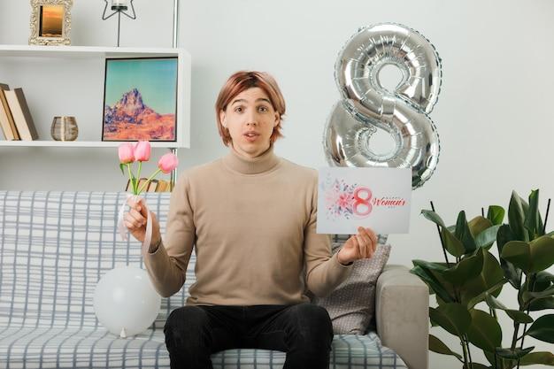 リビングルームのソファに座っているグリーティングカードと花を保持している幸せな女性の日に混乱したハンサムな男