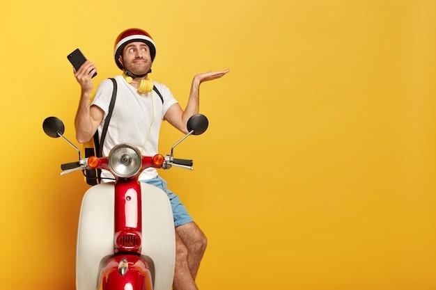 赤いヘルメットとスクーターで混乱したハンサムな男性ドライバー