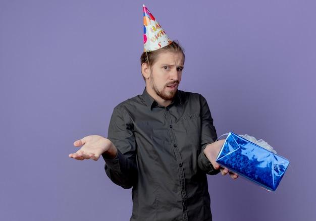 Uomo bello confuso in protezione di compleanno tiene il contenitore di regalo isolato sulla parete viola