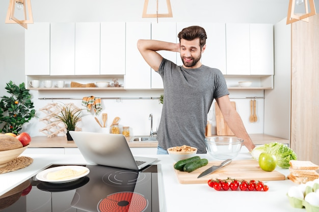 Confused handsome man cooking vegetable salad in kitchen