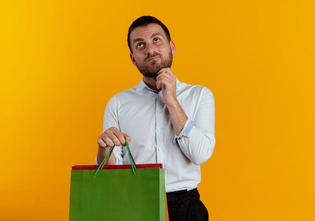 L'uomo bello confuso tiene i sacchetti della spesa di carta mette la mano sul mento che osserva in su isolato sulla parete arancione