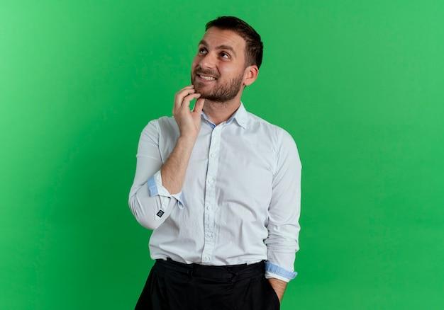L'uomo bello confuso mette la mano sul mento che osserva in su isolato sulla parete verde