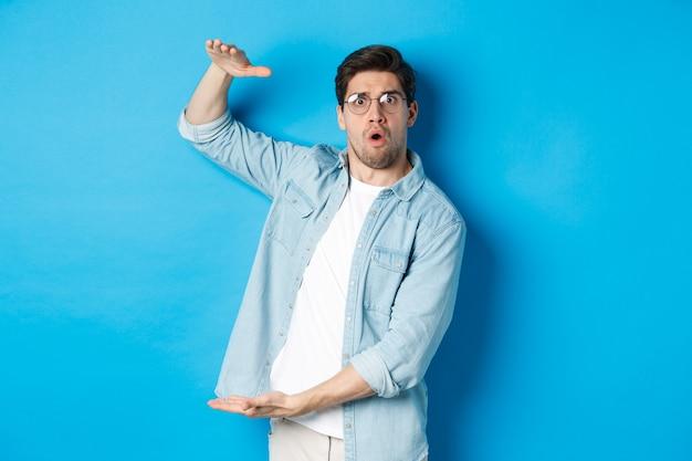 大きなサイズを示し、大きな箱を形作り、驚いて見える、青い背景の上に立っている混乱したハンサムな男