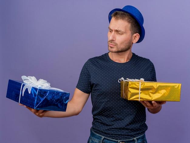Смущенный красавец в синей шляпе держит и смотрит на подарочные коробки, изолированные на фиолетовой стене
