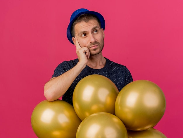 Confused handsome man wearing blue party hat holds helium balloons looking at side isolated on pink wall with copy space