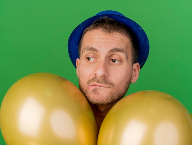Confused handsome man wearing blue party hat stands with helium balloons looking at side isolated on green wall