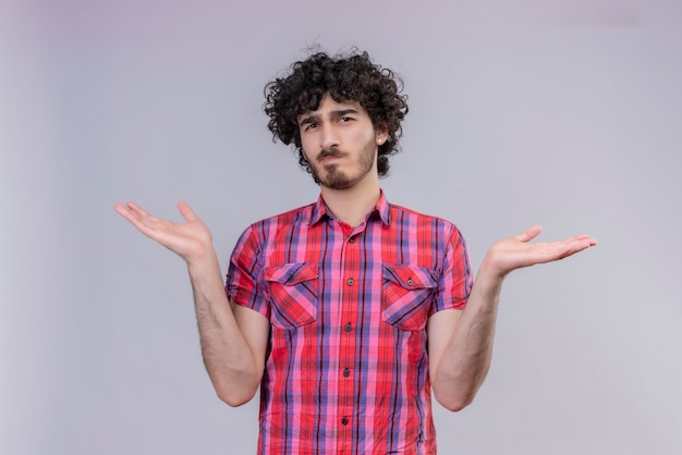Un bell'uomo confuso con i capelli ricci in camicia a quadri, con le braccia aperte
