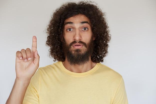 Смущенный красивый молодой бородатый кареглазый мужчина с темными вьющимися волосами, подняв указательный палец вверх и смущенно глядя, сморщил лоб