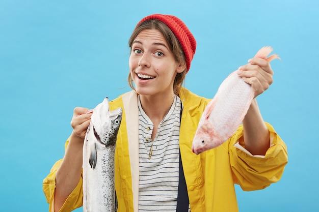 Femmina felice confusa che tiene due pesci che non sanno cosa scegliere