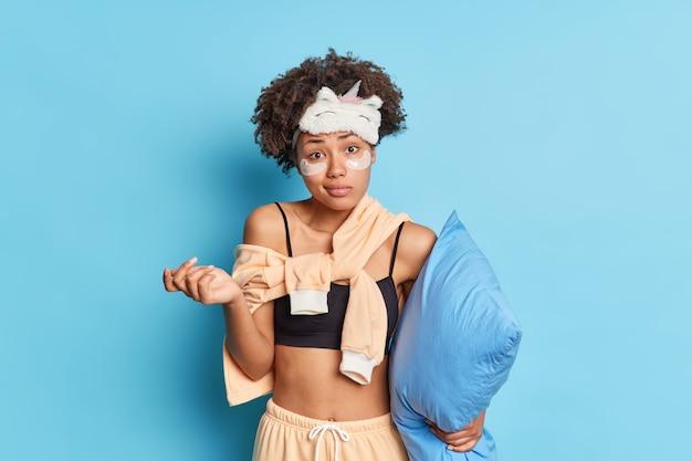 パジャマ姿の混乱した躊躇している若い女性が肩をすくめ、何かが枕を保持していることについて不安を感じている青い壁に向かって屋内に立つ日の計画を知らない