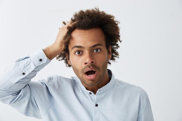 フォーマルな服を着ているアフリカのヘアスタイルで混乱している流行に敏感な男