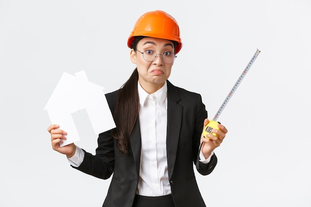Confused indecisive asian female architect dont know what do, engineer in helmet and business suit shrugging while holding home maket and measuring tape, white background