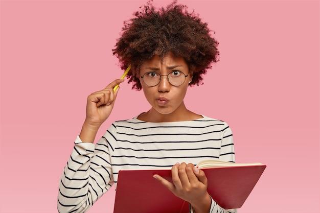 Donna indecisa confusa con pelle nera, capelli ricci, graffi la testa con la matita, vestita con un maglione a righe, porta le labbra