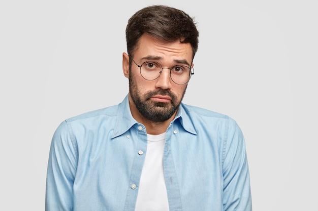 混乱した侮辱的なあごひげを生やした男は悲惨な疑いの表情で見え、人生で真剣な決断をしなければならず、丸いアイウェアと青いシャツを着て、白い壁に立ちます。人と感情の概念