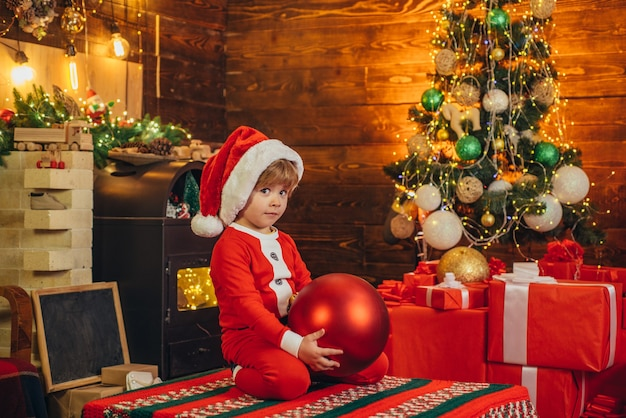 Confused kid is wearing santa clothes, decorating the christmas tree. christmas concept.  christmas child dreams.