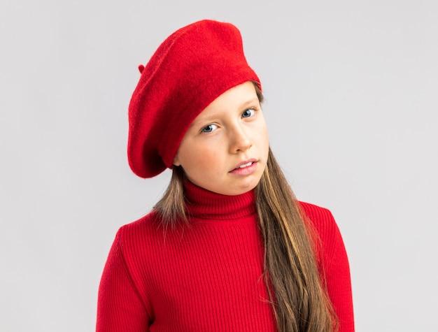 복사 공간이 있는 흰 벽에 격리된 빨간 베레모를 입은 혼란스러운 금발 소녀