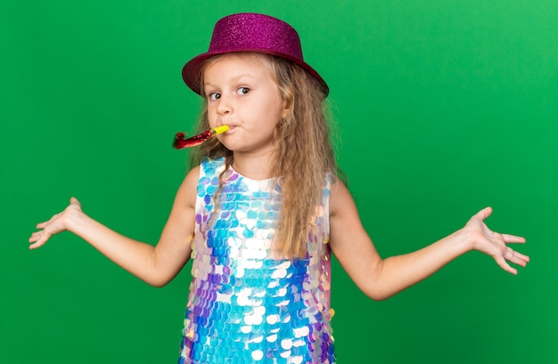 Сбитая с толку маленькая блондинка с фиолетовой шляпой дует свисток и держит руки открытыми, изолированными на зеленой стене с копией пространства