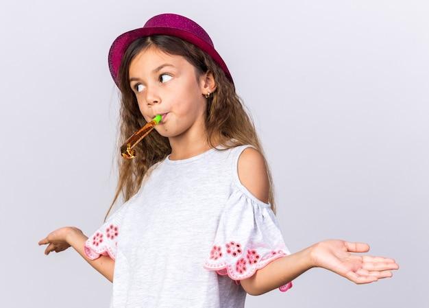 Запутанная маленькая кавказская девушка с фиолетовой шляпой, дует свисток, глядя в сторону, изолированную на белой стене с копией пространства