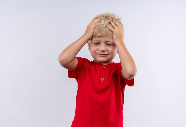 Un ragazzino biondo sveglio confuso in maglietta rossa che tiene la testa tra le mani mentre guarda un muro bianco