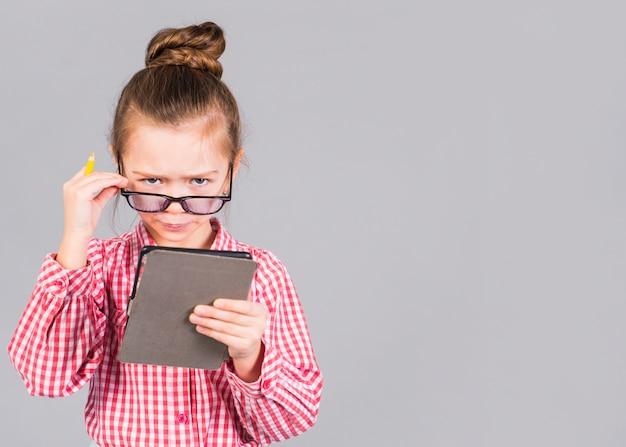 Путать маленькая девочка в очках с помощью планшета