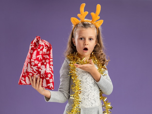 Confused little girl wearing christmas hair hoop with garland on neck holding and points at christmas bag isolated on blue background