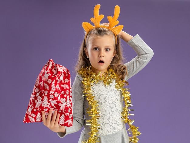 青い背景で隔離の頭に手を置くクリスマスバッグを保持している首に花輪とクリスマスの髪のフープを身に着けている混乱した少女