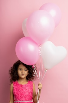 Растерянная маленькая девочка с кудрявыми волосами, в красивом платье, с белыми и розовыми воздушными шарами в руках, со смущенным взглядом