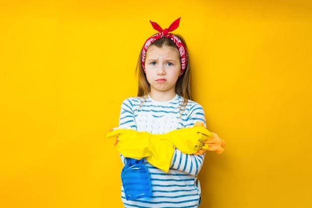 Путать домохозяйка 9-10 маленькой девочки в фартуке держит губку и бутылку с моющим средством для мытья посуды, делая работу по дому, изолированную на желтой стене фон студии. концепция домашнего хозяйства
