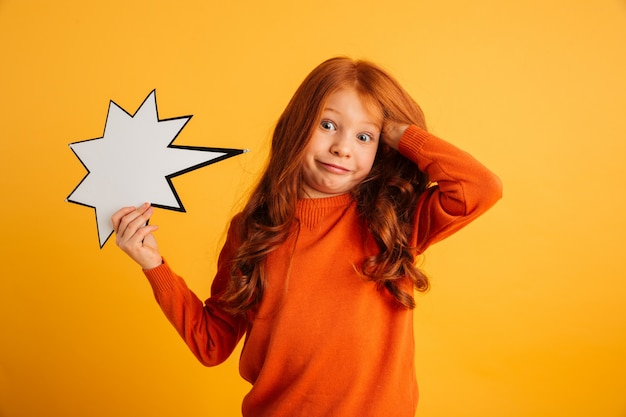 Confused little redhead girl holding speech bubble.