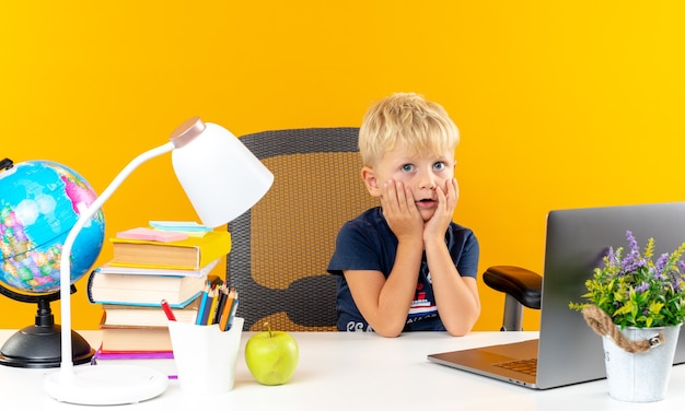 頬に手を置く学校の道具でテーブルに座っている混乱した小さな男子生徒