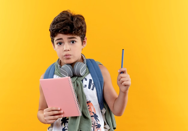 Confused little school boy wearing back bag and headphones holding notebook with pen isolated on yellow background
