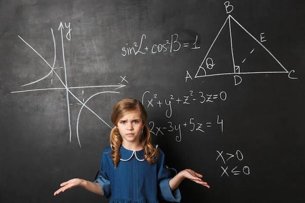 Confused little schoolgirl standing at the blackboard with math graphics written on it