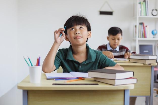 Смущенный мальчик начальной школы при сдаче экзаменов в классе