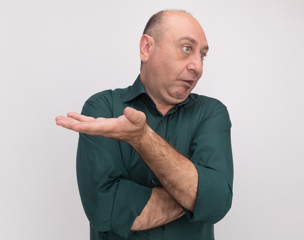 흰색 벽에 고립 된 카메라에 손을 들고 녹색 티셔츠를 입고 측면 중년 남자를보고 혼란