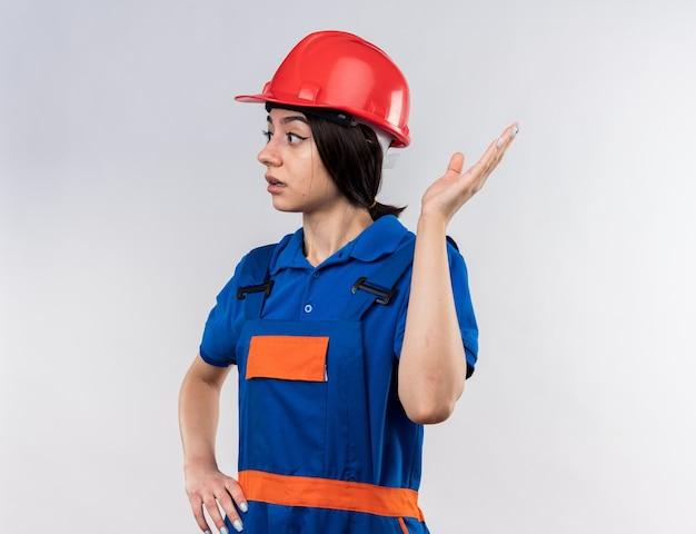 Смущенный глядя на сторону молодой женщины-строителя в форменных очках с рукой на стороне
