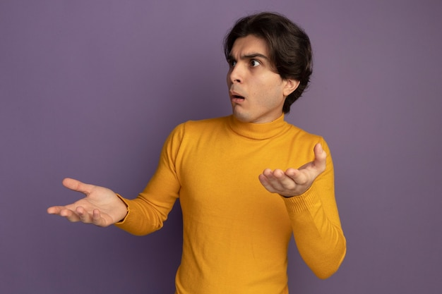 보라색 벽에 고립 된 손을 확산 노란색 터틀넥 스웨터를 입고 측면 젊은 잘 생긴 남자를보고 혼란