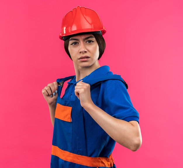 Confused looking at camera young builder woman in uniform holding uniform
