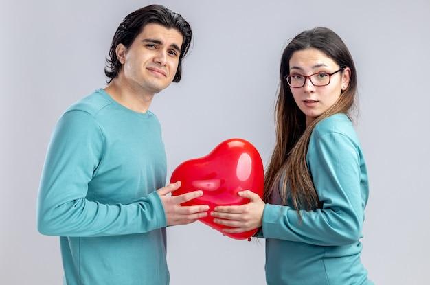 Confuso guardando la telecamera giovane coppia il giorno di san valentino che tiene il palloncino del cuore isolato su sfondo bianco white