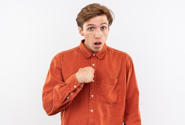 赤いシャツを着て混乱している正面の若いハンサムな男は、白い壁に隔離された自分を指しています
